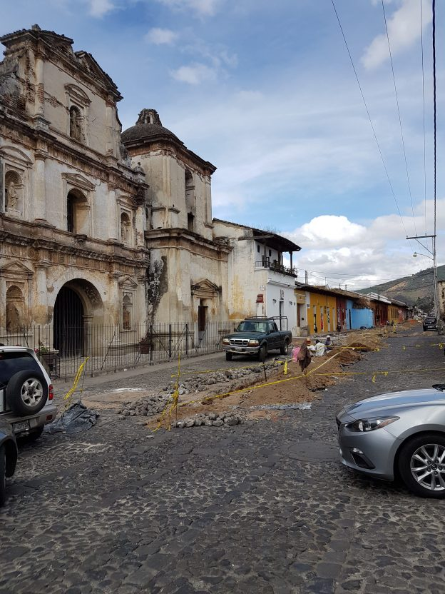 Image of cobbestoned road being dug up for repairs and ruined stone buildings in the street of Antigua, Guatemala