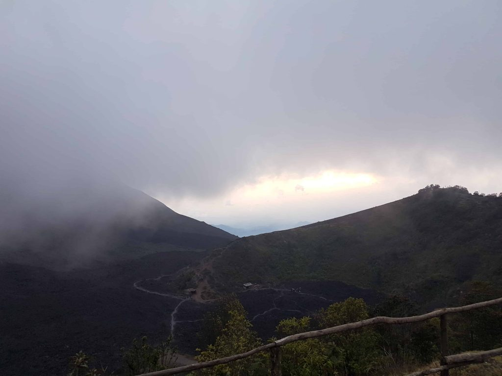 View at the top of Volcan Pacaya. Image shows black lava landscape and heavy mist
