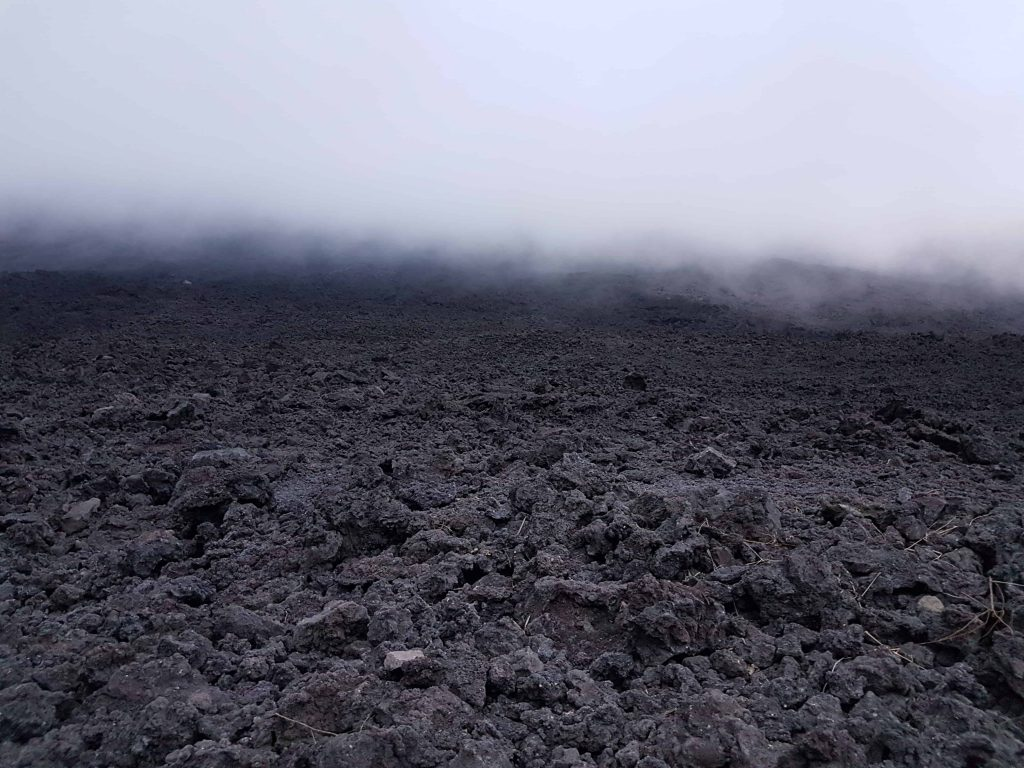 Image of the sharp, solidified lava landscape at the top of Volcan Pacaya with mist settled on top