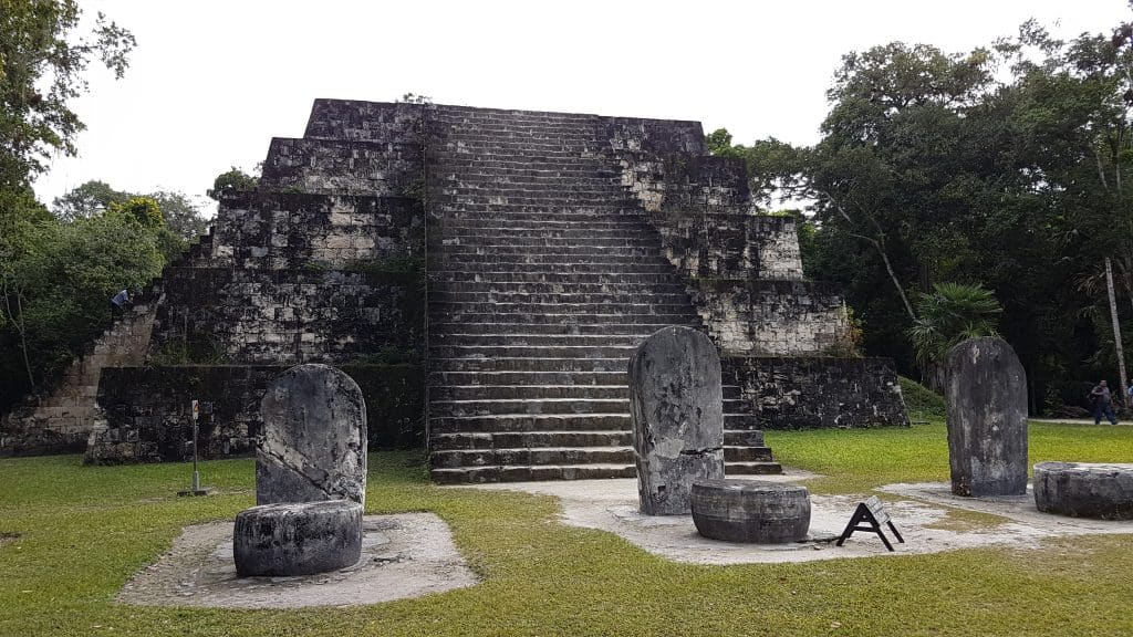 The east Pyramid of Complex Q at Tikal Guatemala. Structure is a flat top pyramid with steps leading to the top on the front. In front of the Pyramid are a series of upright stone tablets