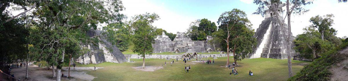 Panoramic shot of the Great Plaza of Tikal as seen from the Central Acropolis. The North Acropolis is straight across the clearing, with Temple I bordering the clearing on the right and Temple II on the left