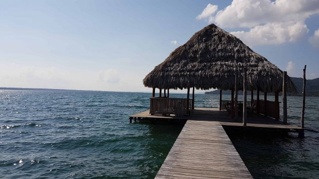 Image depicts a thatched roof hut at the end of a boardwalk situated on the water of a lake in Guatemala
