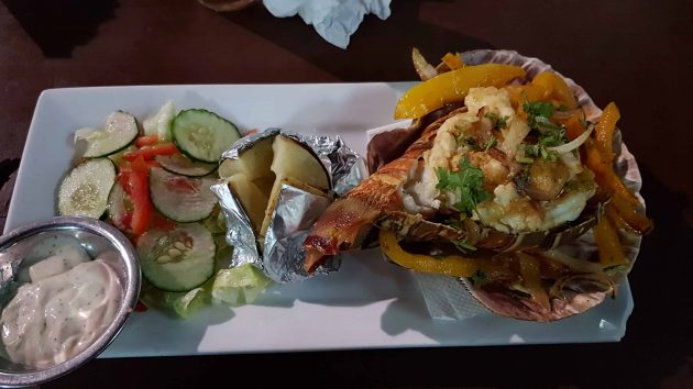A lobster meal in San Ignacio, served in garlic butter with baked potato and salad