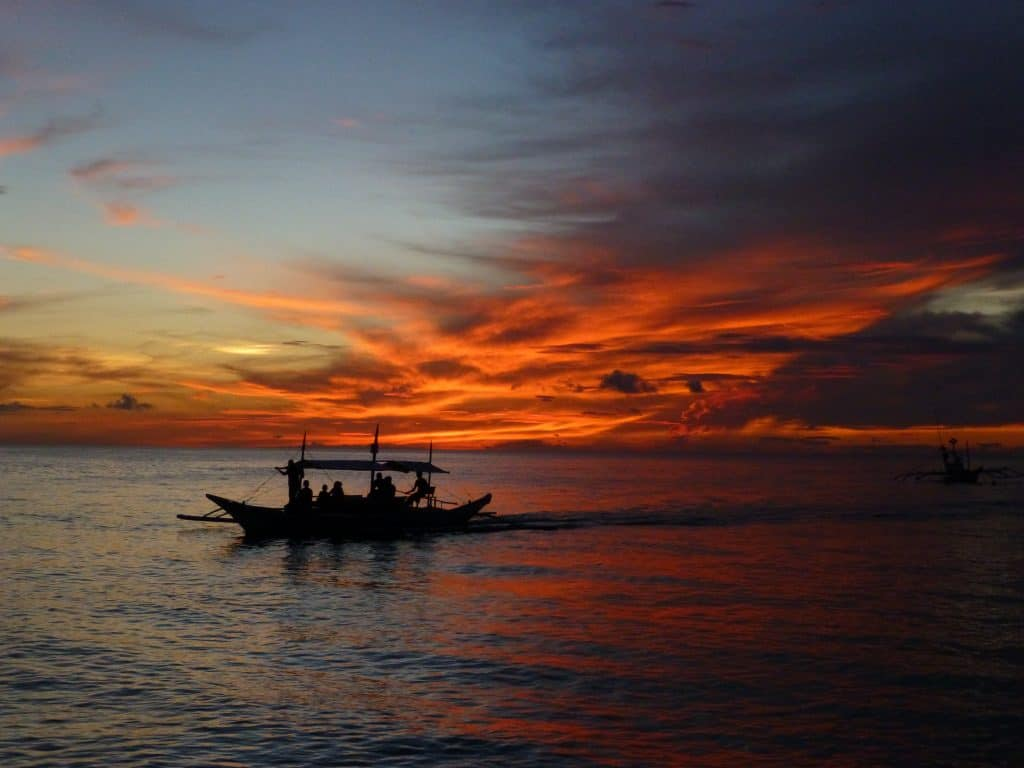Fishing boat with setting sunset sky behind, Boracay Philippines