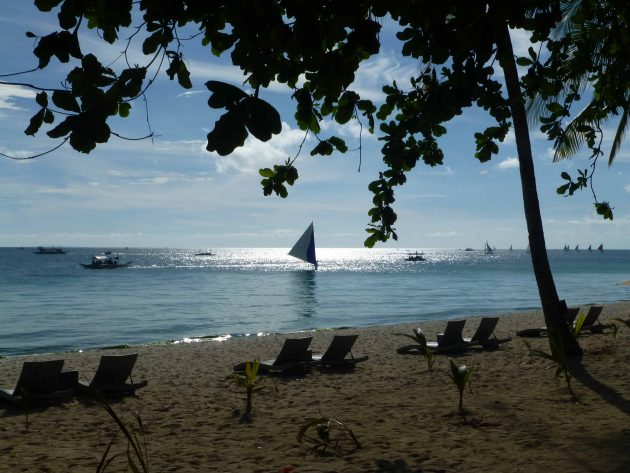 Sailboat on the water beyond lounge chairs on White Beach Boracay, Philippines