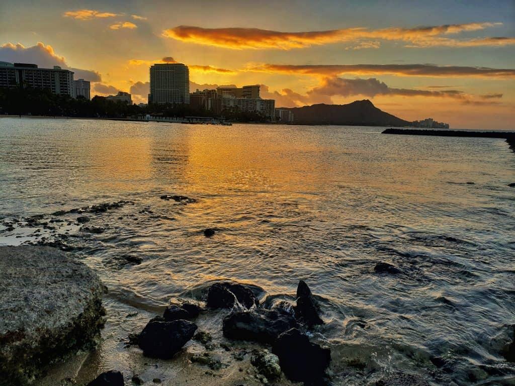 Image of sunrise over Waikiki taken from the rock jetty behind the Hilton Hawaiian Village