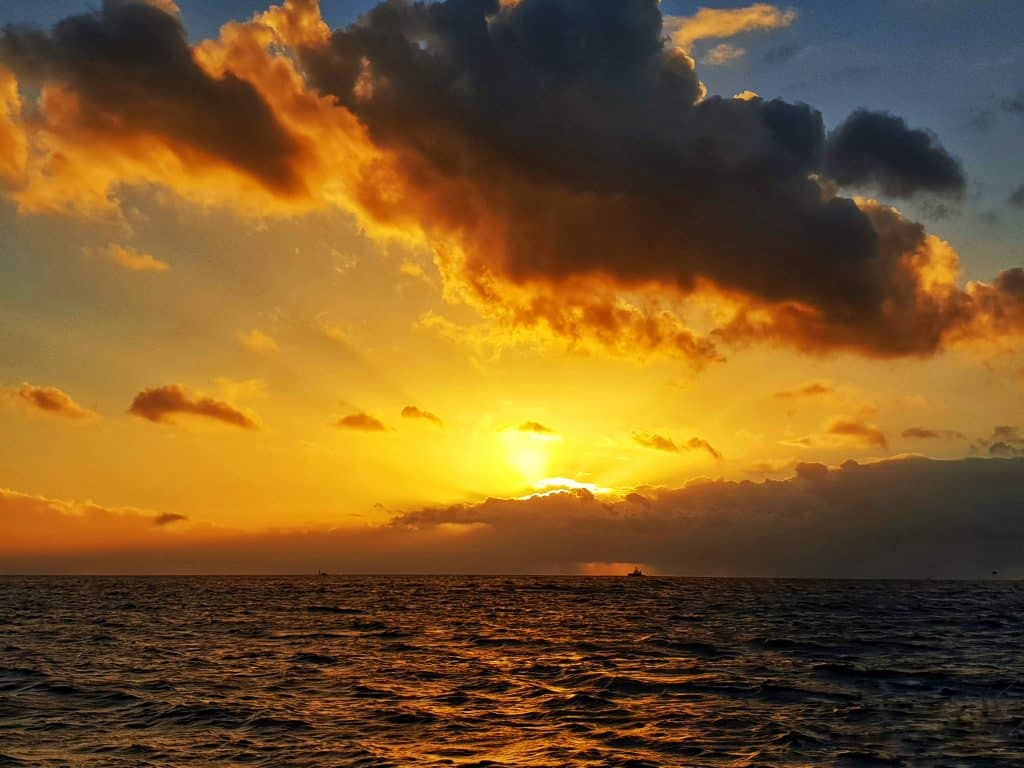 Sun setting over the water on cruise out of Honolulu