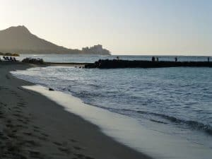 Waves washing up on beach strolling towards Waikiki Beach