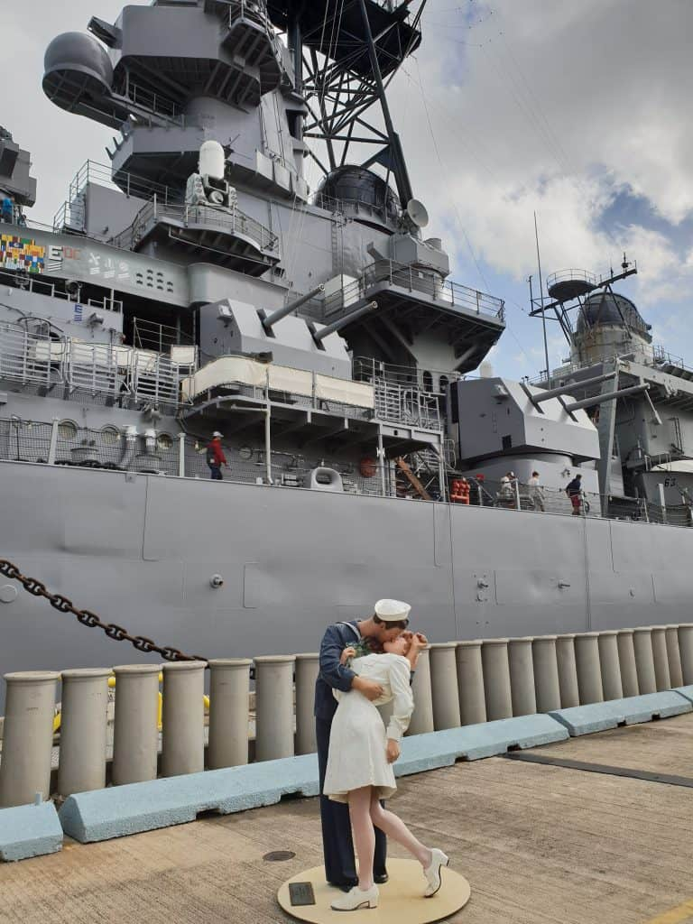 A sculpture of a sailor kissing a woman, replica of a famous photo marking the end of WW2, stands on the dock in front of the USS Missouri