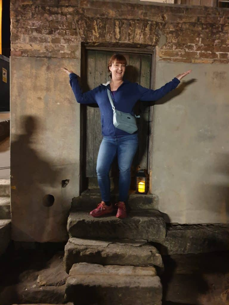Standing in the doorway of number 64 Susannah Place, The Rocks, on Lantern Ghost Tour Sydney