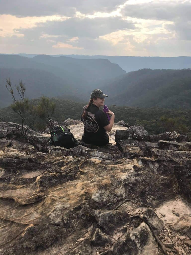 Person sitting on rocky outcrop looking out over valley and mountains on hike to Lockleys Pylon Blue Mountains