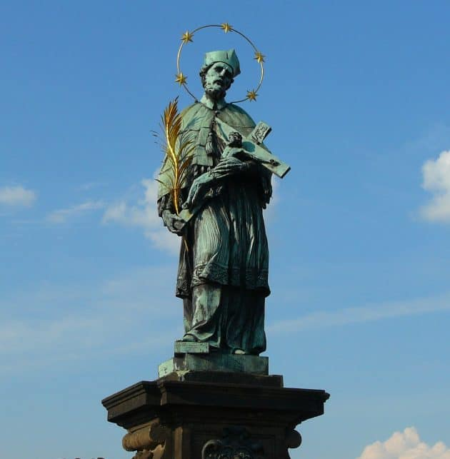 Statue of John of Nepomuk on the Charles Bridge in Prague, a priest holding a crucific and haloed by 5 stars