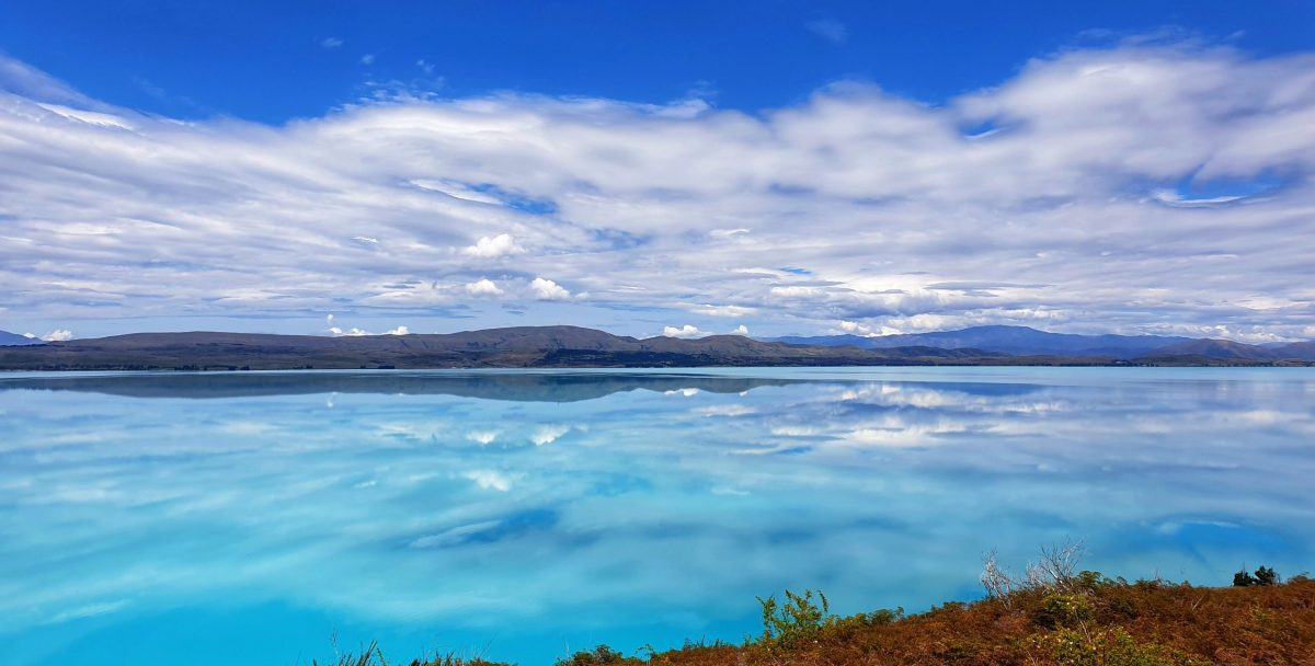 Reflections of sky, clouds and mountains reflected on the surface of Lake Pukaki in New Zealand