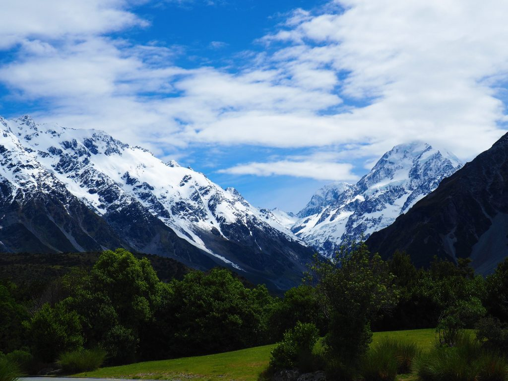 Snow capped mountains behind green fields near Mt Cook in New Zealand