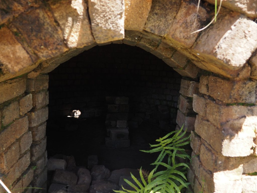 close up of interior of the kiln from doorway, showing large open space and stacked bricks in the middle of the floor