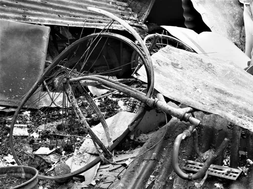 Black and White image of a scorched and twisted bicycle in the rubble of a burnt house after the Grose Valley fire