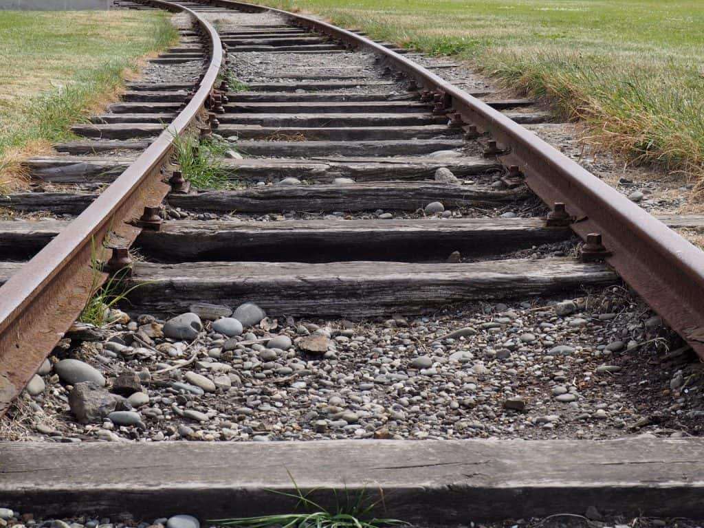 Image of train tracks bordered by grass at Holmes Wharf on New Zealands South Island