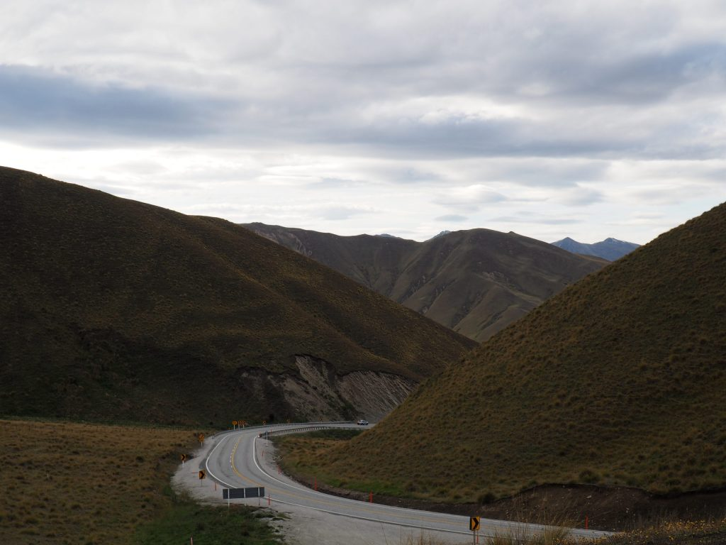 Image of single lane motorway winding through hilly landscape on New Zealands South Island