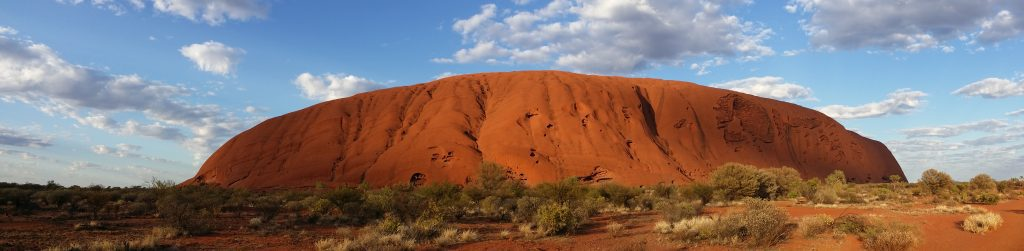 Panorama image of Uluru in Central Australia. Sun is hitting the rock and there are clouds in the sky behind and above the rock.