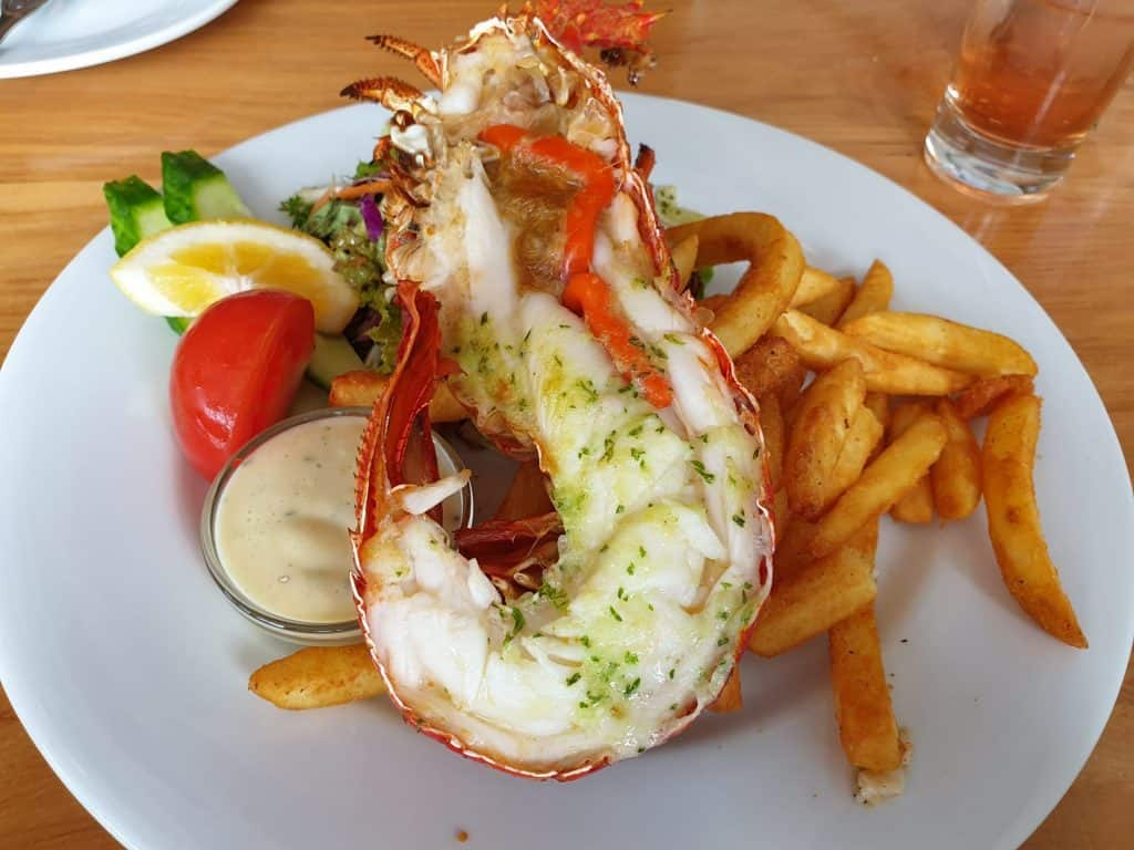 A half lobster, chips and salad in Kaikoura. Kaikoura is known for its seafood.