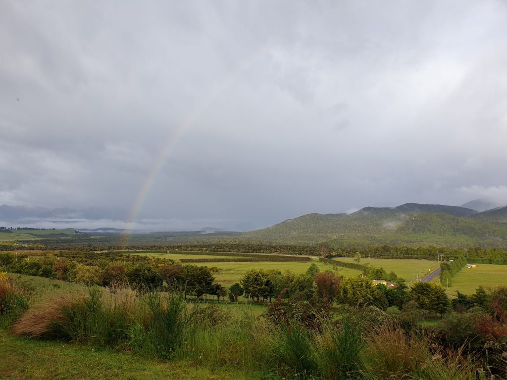 Rainbow in Te Anau stretching over fields with mountain ranges in the background