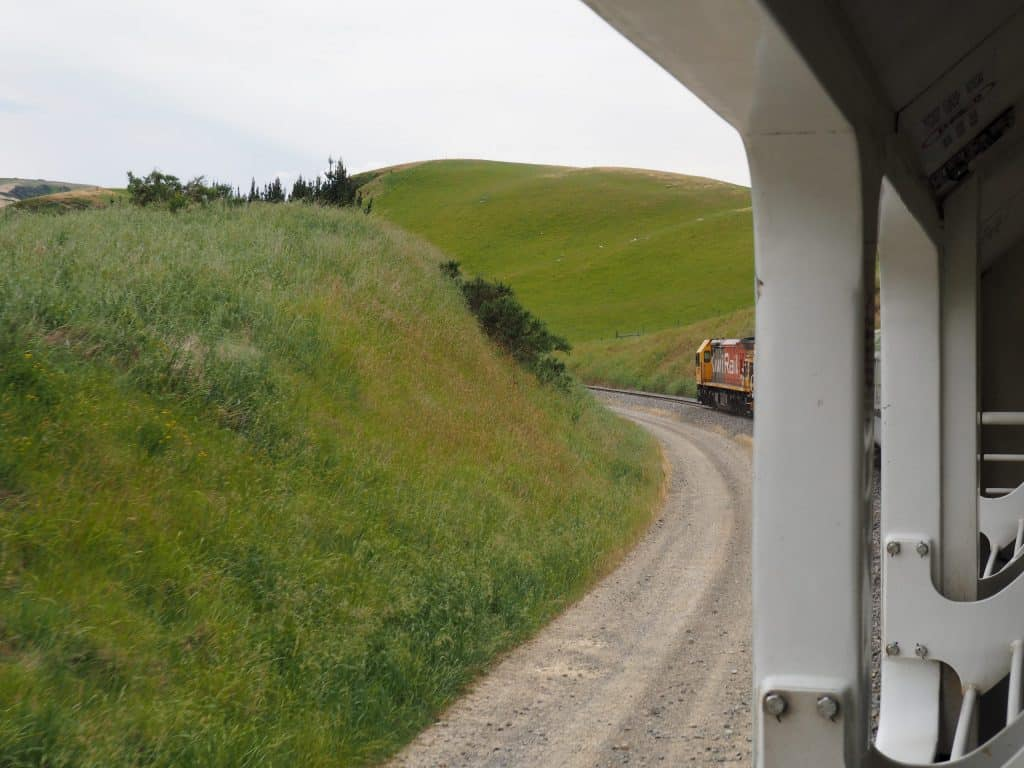 Image taken from within the open carriage of the Tranz Pacific train. The engine is seen winding through the hills pulling the train behind it