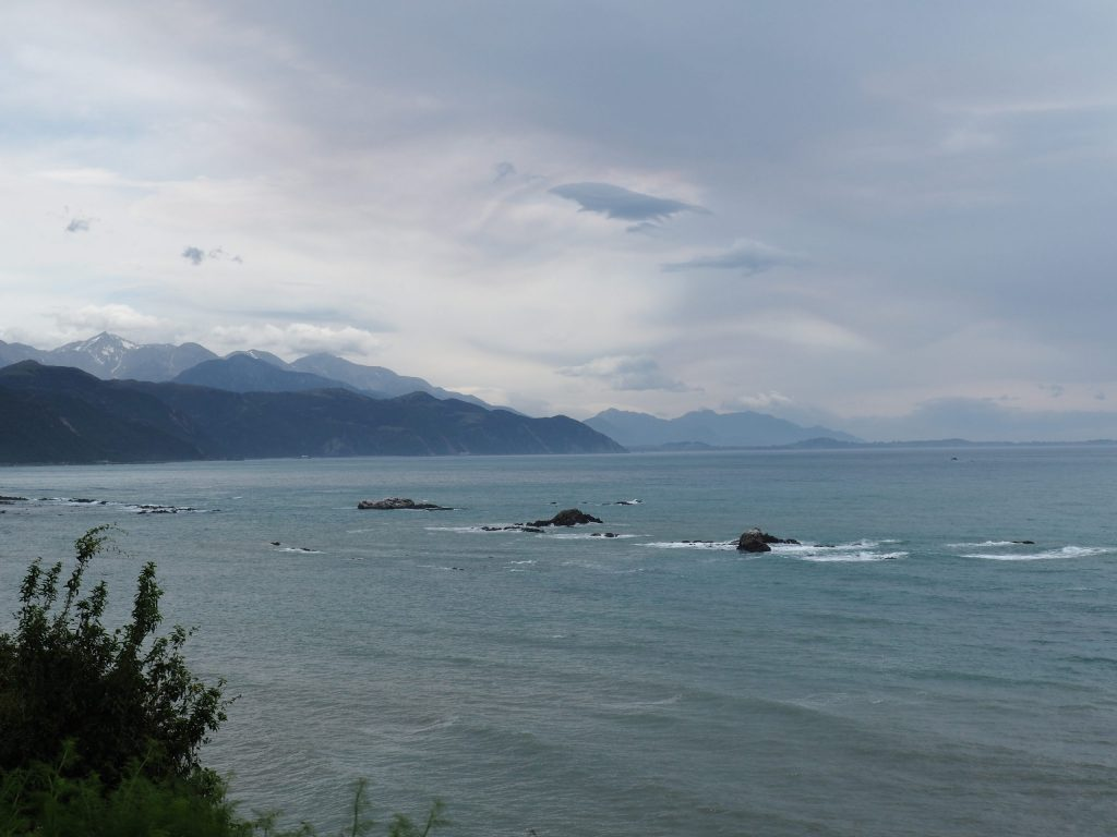 The Pacific ocean and the New Zealand coastline stretching behind it as captured from the Tranz Pacific