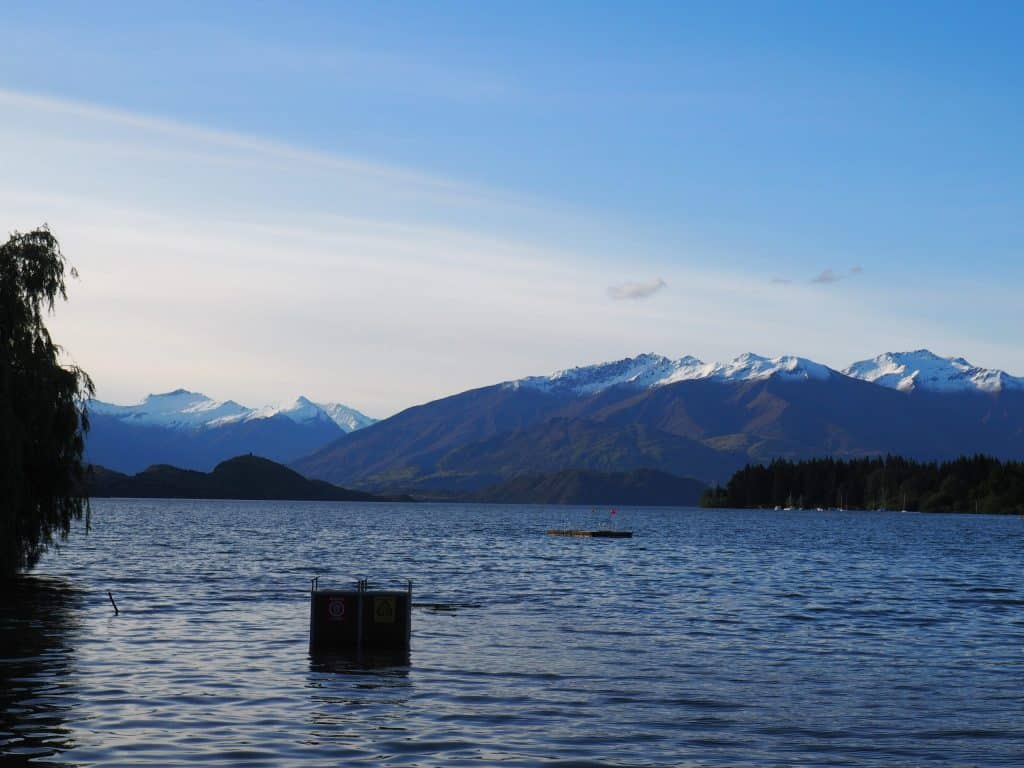 Garbage bins standing out in the water at Lake Wanaka, with the snow capped Southern Alps behind